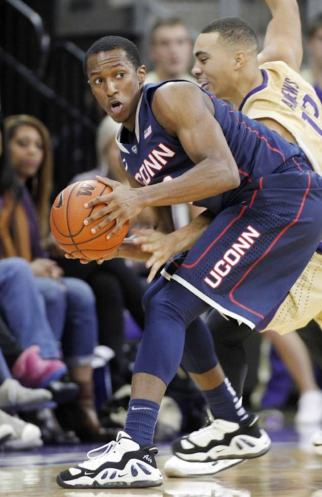 Connecticut's Lasan Kromah, left, gains control of a lose ball with Washington's Andrew Andrews behind in the second half of a NCAA college basketball game in Seattle on Sunday, Dec. 22, 2013. UConn won 82-70