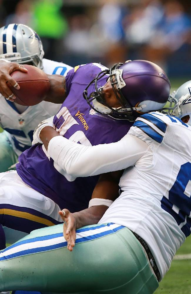 Minnesota Vikings running back Adrian Peterson (28) is tackled by Dallas Cowboys defensive end Jarius Wynn (92) and Justin Durant (52) during the second half of an NFL football game Sunday, Nov. 3, 2013, in Arlington, Texas