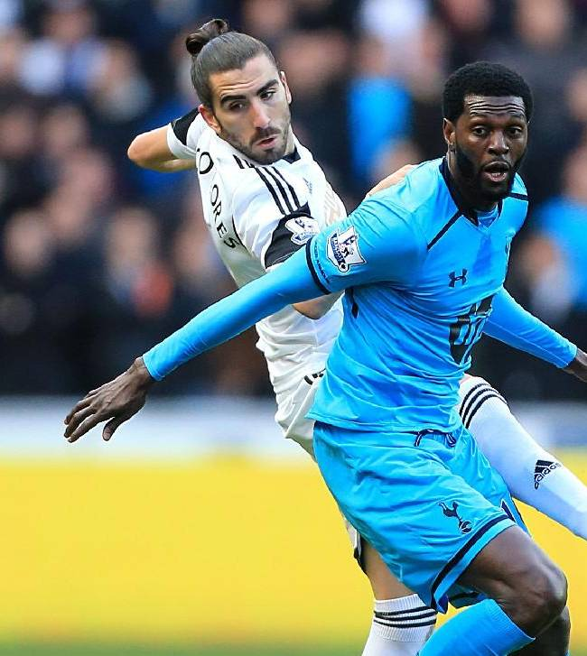 Swansea City's Chico, left, and Tottenham Hotpspur's Emmanuel Adebayor  battle for the ball  during their  English Premier League soccer match, at the Liberty Stadium, Swansea, Wales, Sunday Jan. 19, 2014