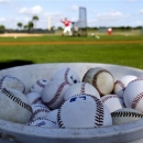 Baseballs sit in a bucket as St. Louis Cardinals batting practice pitcher Dennis Schutzenhofer, top center, throws batting practice before the start of spring training baseball, Monday, Feb. 11, 2013, in Jupiter, Fla. The Cardinals will open up camp this week with the first pitchers and catchers workout. (AP Photo/Julio Cortez)