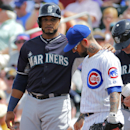 Seattle Mariners' Robinson Cano, left, rubs the neck of Chicago Cubs' Ryan Roberts after a base hit during the first inning of a spring training baseball game, Thursday, March 20, 2014, in Mesa, Ariz The Associated Press