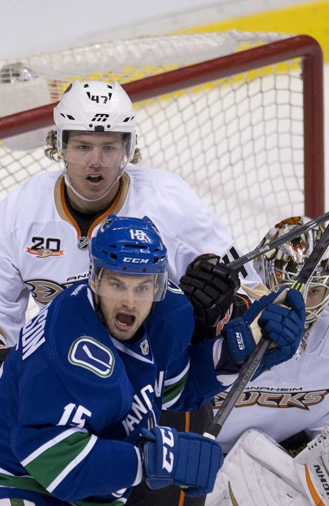 Vancouver Canucks center Brad Richardson (15) tries to get a shot on Anaheim Ducks goalie John Gibson (36) as Anaheim Ducks Hampus Lindholm (47) looks on during the first period of NHL hockey action in Vancouver, British Columbia, on Monday, April 7, 2014