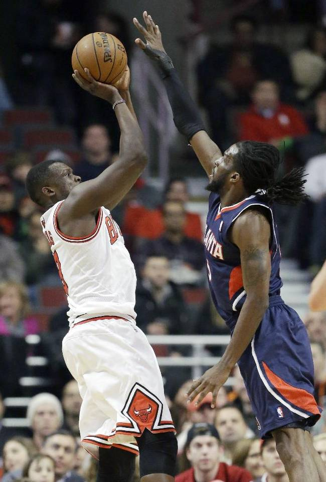 Chicago Bulls forward Luol Deng, left, shoots over Atlanta Hawks forward DeMarre Carroll during the first half of an NBA basketball game in Chicago on Saturday, Jan. 4, 2014
