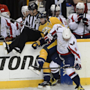 Washington Capitals right wing Alex Ovechkin (8), of Russia, checks Nashville Predators forward Mike Fisher (12) into the boards as linesman Brad Lazarowich, left, tries to get out of the way in the second period of an NHL hockey game on Sunday, March 30,