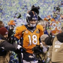 In this Feb. 2, 2014 file photo, Denver Broncos quarterback Peyton Manning walks off the field after the Broncos lost to the Seattle Seahawks in the NFL Super Bowl XLVIII football game in East Rutherford, N.J. Manning delivers the keynote address at the B