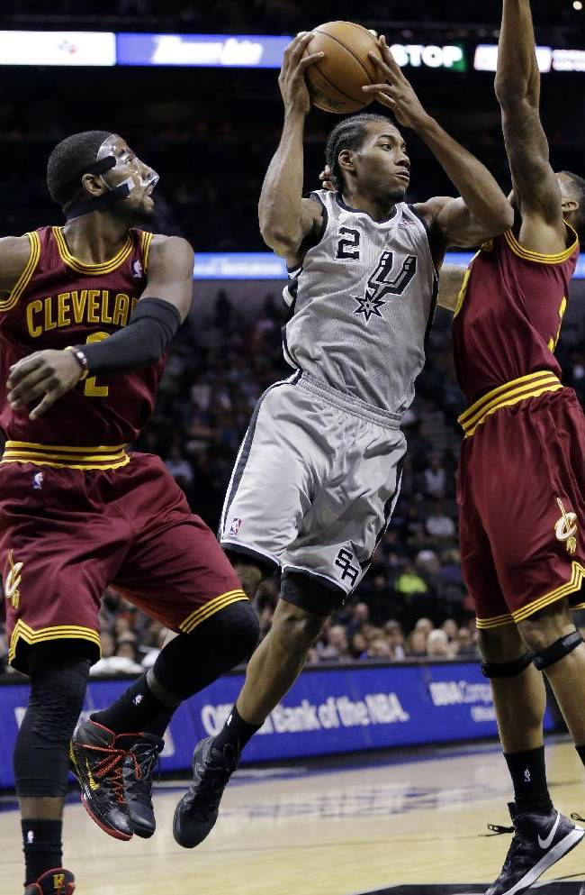 San Antonio Spurs' Kawhi Leonard, center, drives between Cleveland Cavaliers' Kyrie Irving, left, and Alonzo Gee, right, during the first half of an NBA basketball game Saturday, Nov. 23, 2013, in San Antonio