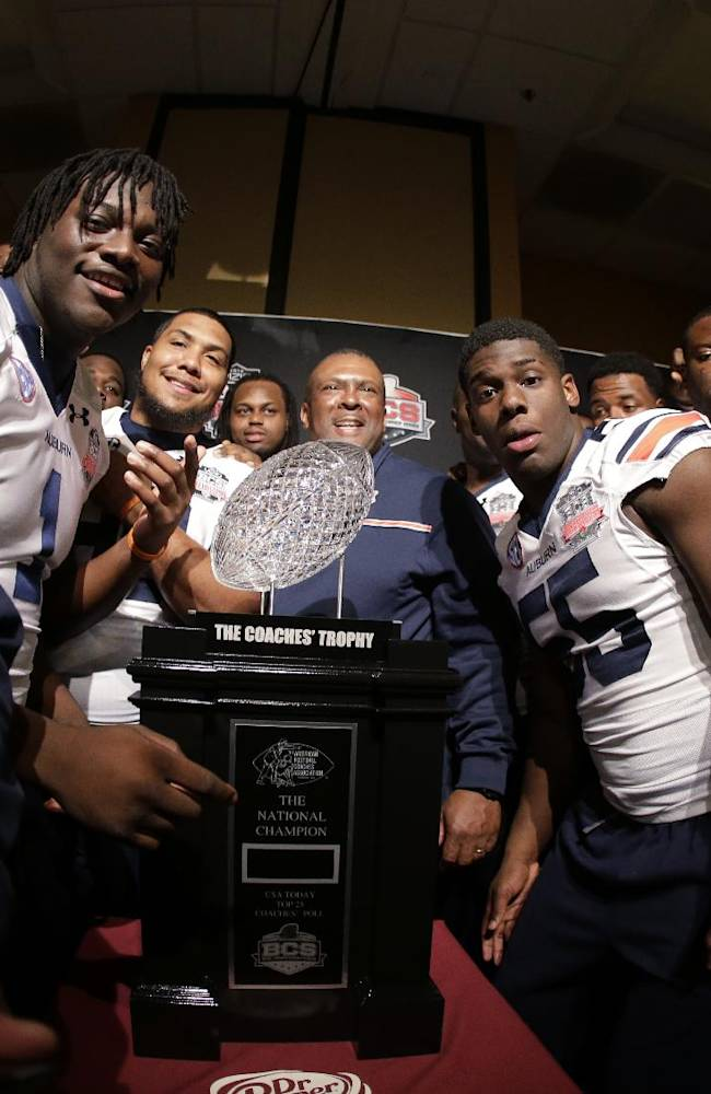Auburn players pose with The Coaches' Trophy during media day for the NCAA BCS National Championship college football game Saturday, Jan. 4, 2014, in Newport Beach, Calif. Florida State plays Auburn on Monday, Jan. 6, 2014