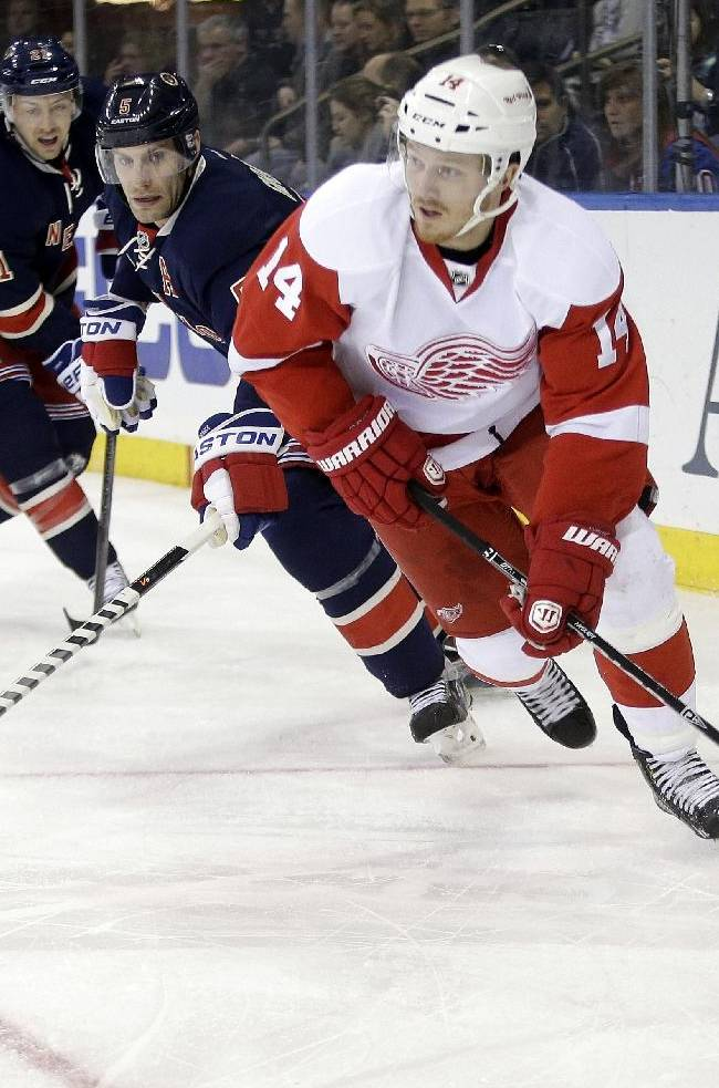 Detroit Red Wings' Gustav Nyquist (14), of Sweden, passes away from New York Rangers' Dan Girardi, center, and Derek Stepan (21) during the first period of an NHL hockey game Sunday, March 9, 2014, in New York