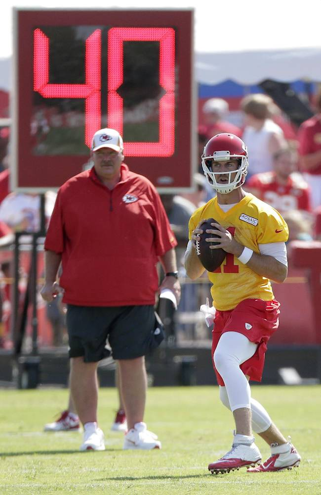 Kansas City Chiefs coach Andy Reid watches while quarterback Alex Smith looks for a receiver during NFL football training camp Thursday, July 24, 2014, in St. Joseph, Mo