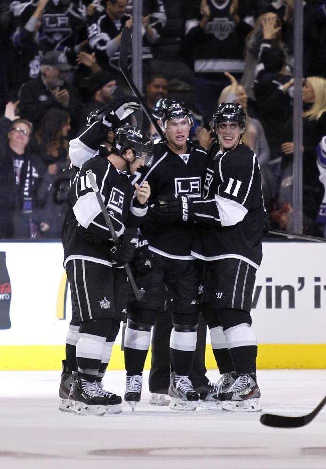 Los Angeles Kings centers Mike Richards, left, and Anze Kopitar (11), of Yugoslavia, celebrate an overtime goal by  Kings center Jeff Carter, center, defeating the Ottawa Senators left wing Clarke MacArthur (16) skating by in their NHL hockey game, Wednesday, Oct. 9, 2013, in Los Angeles. Kings won the game 4-3 in overtime,
