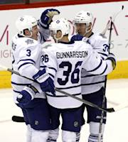 Toronto Maple Leafs defenseman Carl Gunnarsson (36) celebrates with Dion Phaneuf (3) and Carter Ashton (37) after scoring a second period goal against the Phoenix Coyotes during an NHL hockey game, Monday, Jan. 20, 2014, in Glendale, Ariz. (AP Photo/Rick Scuteri)
