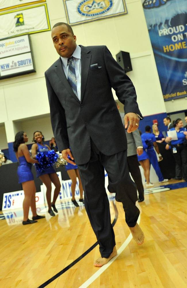In this photo taken on Jan. 12, 2012, Georgia State coach Ron Hunter, barefoot, walks out to the court for of an NCAA college basketball game against North Carolina-Wilmington in Atlanta. Hunter coaches one game each year barefooted to bring attention to his charity that provides shoes to millions of poor children around the world