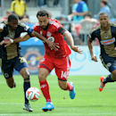 Toronto FC's Dwayne De Rosario, center, fights for the ball against Philadelphia Union's Raymon Gaddis during the first half of an MLS soccer game on Saturday Sept. 6, 2014 in Toronto The Associated Press