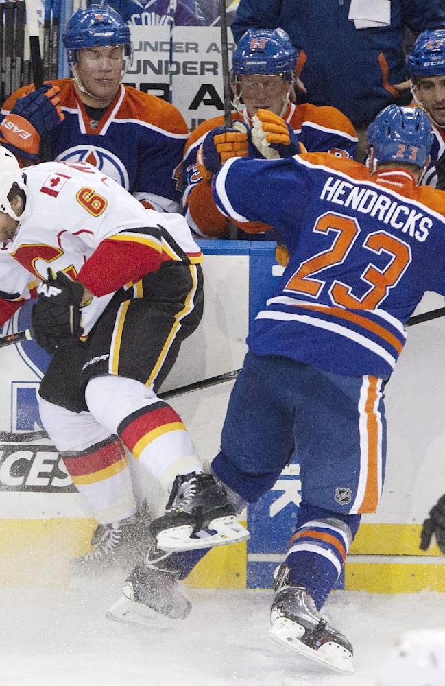Calgary Flames' Dennis Wideman (6) is checked by Edmonton Oilers' Matt Hendricks (23) during the second period of an NHL hockey game Saturday, March 1, 2014, in Edmonton, Alberta