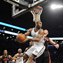 Brooklyn Nets' Alan Anderson (6) looks to pass the ball away from Toronto Raptors' Jonas Valanciunas (17) in the first half of an NBA basketball game on Monday, March 10, 2014 at Barclays Center in New York The Associated Press