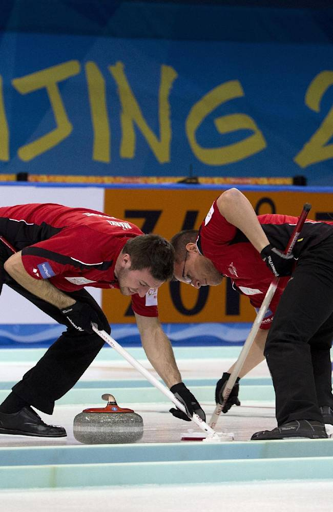 Switzerland's Valentin Tanner, right, and Dominik Marki sweep the path for the stone during their bronze medal match against Canada at the World Men's Curling Championship at the Capital Gymnasium in Beijing, China Sunday, April 6, 2014. Switzerland defeated Canada 7-5