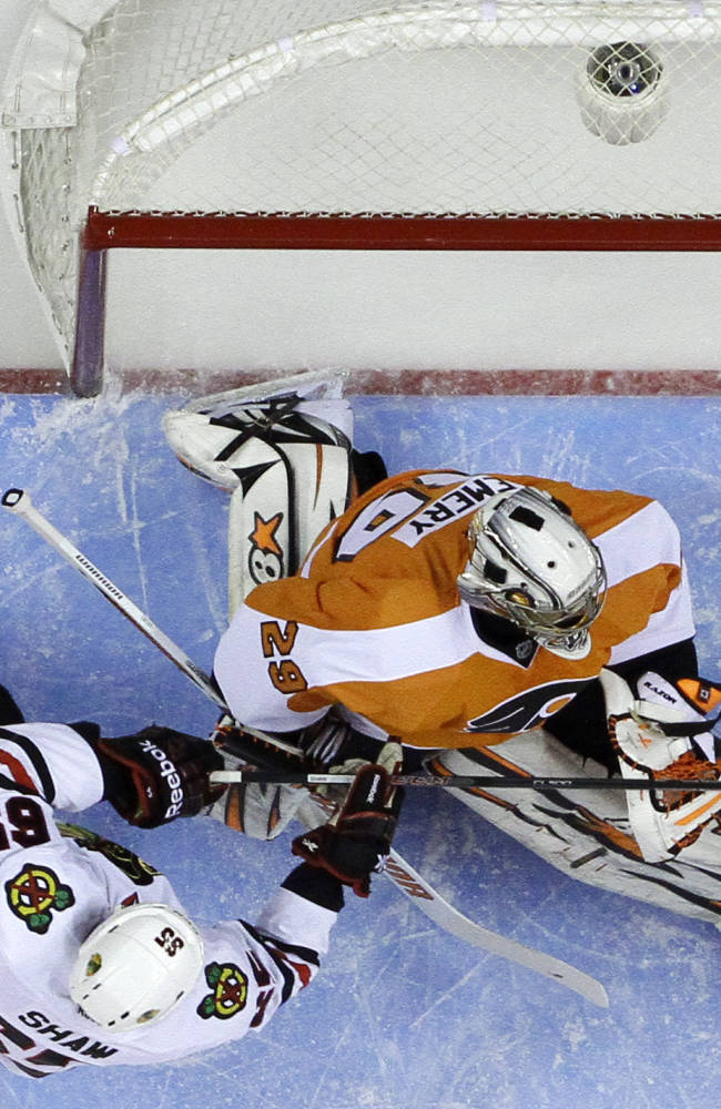 Chicago Blackhawks' Andrew Shaw, left, scores a goal past Philadelphia Flyers' Ray Emery during the first period of an NHL hockey game, Tuesday, March 18, 2014, in Philadelphia