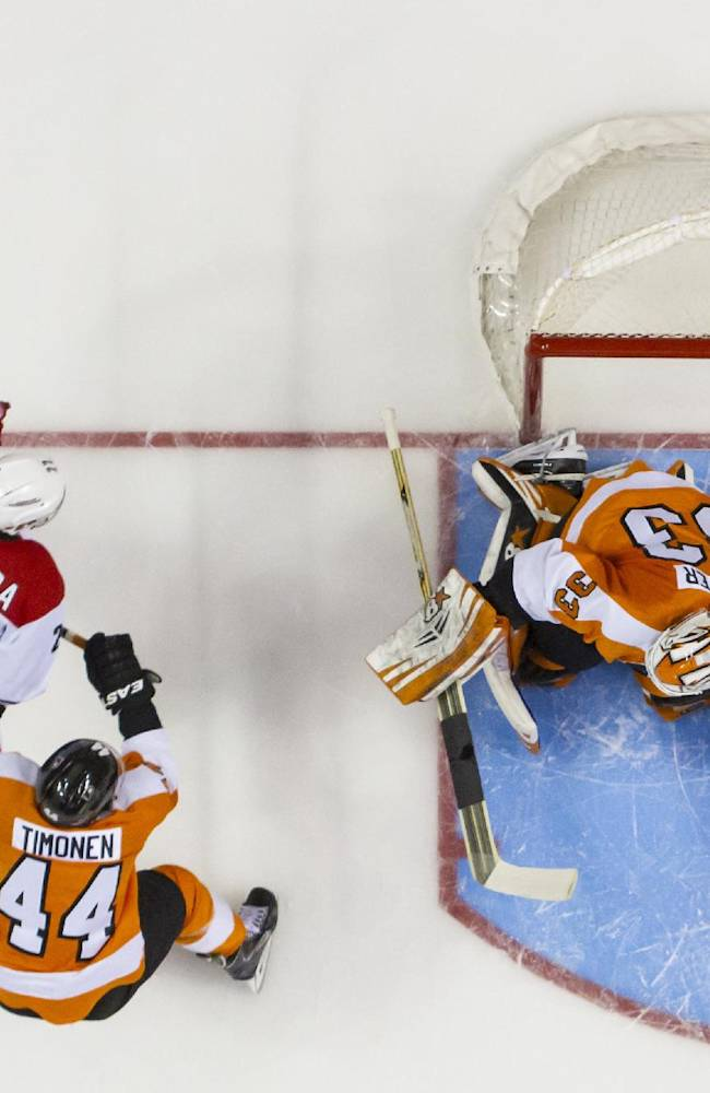 Carolina Hurricanes' Manny Malhotra, left, scores a goal on Philadelphia Flyers goalie Cal Heeter, right, as  Kimmo Timonen watches during the first period of an NHL hockey game, Sunday, April 13, 2014, in Philadelphia