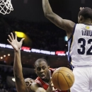 Houston Rockets' James Anderson (5) passes the ball between Memphis Grizzlies' Ed Davis (32) and Darrell Arthur during the first half of an NBA basketball game in Memphis, Tenn., Friday, March 29, 2013. (AP Photo/Danny Johnston)