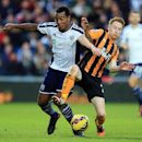 West Bromwich Albion's Andre Wisdom, left, battles for the ball with Hull City's Stephen Quinn during the English Premier League soccer match at The Hawthorns, West Bromwich, England, Saturday Jan. 10, 2015