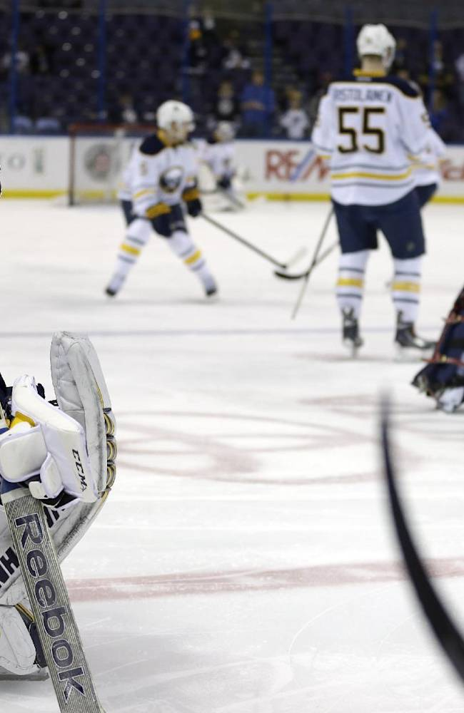 St. Louis Blues goalie Ryan Miller, left, looks on as members of his old team, the Buffalo Sabres, skate during warm ups before an NHL hockey game on Thursday, April 3, 2014, in St. Louis. Miller is not scheduled to play in the game