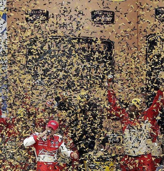 Driver Kevin Harvick celebrates in victory lane after winning the NASCAR Sprint Cup series auto race at Kansas Speedway in Kansas City, Kan., Sunday, Oct. 6, 2013