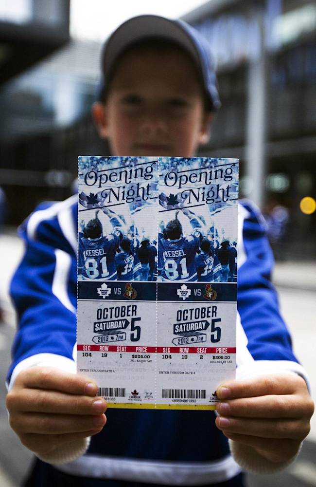 Bradley Backus holds his opening day tickets in Maple Leaf Square before the Toronto Maple Leafs play the Ottawa Senators in in an NHL hockey game in Toronto, Saturday, Oct. 5, 2013. (AP photo/The Canadian Press, Mark Blinch)