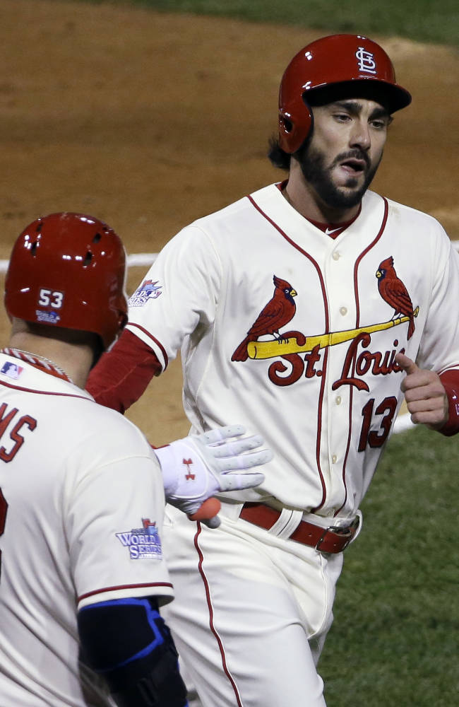 St. Louis Cardinals' Matt Carpenter (13) is congratulated by teammate Matt Adams after scoring during the first inning of Game 3 of baseball's World Series against the Boston Red Sox Saturday, Oct. 26, 2013, in St. Louis