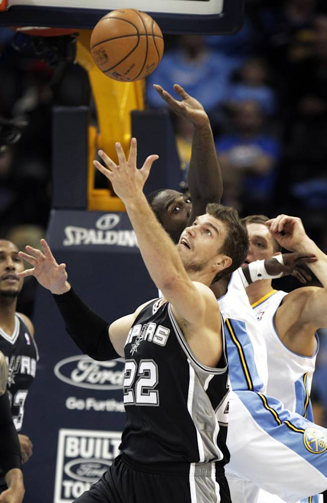 San Antonio Spurs center Tiago Splitter (22) reaches for a loose ball against Denver Nuggets forward J.J. Hickson (7), left, in the second quarter of a basketball game in Denver on Tuesday, Nov. 5, 2013