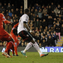 Liverpool's Kolo Toure, center, scores an own goal as Fulham's Darren Bent, right, looks on during their English Premier League soccer match at Craven Cottage, London, Wednesday, Feb. 12, 2014