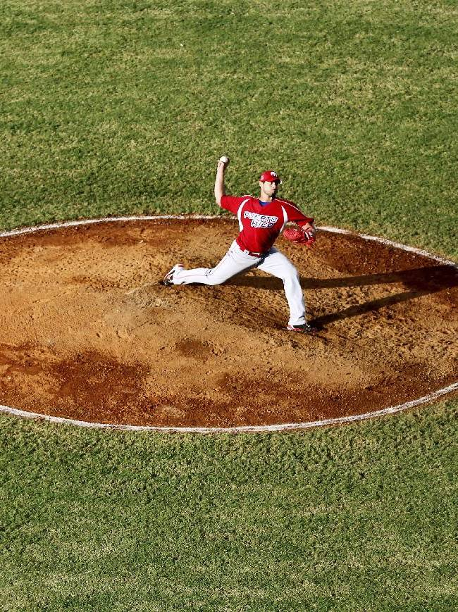 Puerto Rico pitcher Joel Pinero winds up to throw in the fourth inning of a Caribbean Series baseball game against Cuba in Porlamar, Venezuela, Tuesday, Feb. 4, 2014