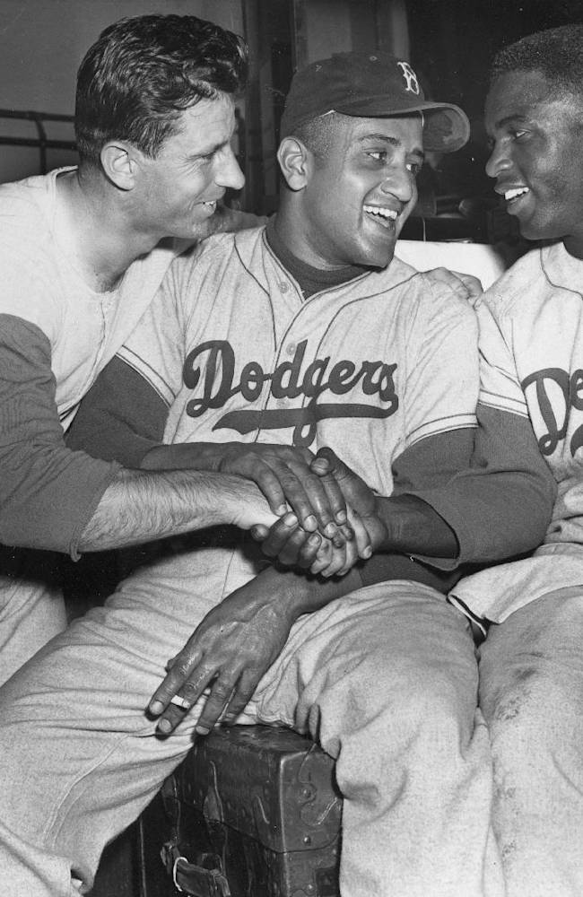 In this Sept. 29, 1951 file photo, Brooklyn Dodgers baseball player Andy Pafko, left, Don Newcomb, center, and Jackie Robinson shake hands in their dressing room after the Dodgers beat the Philadelphia Phillies 5-0, in New York. That flowing blue