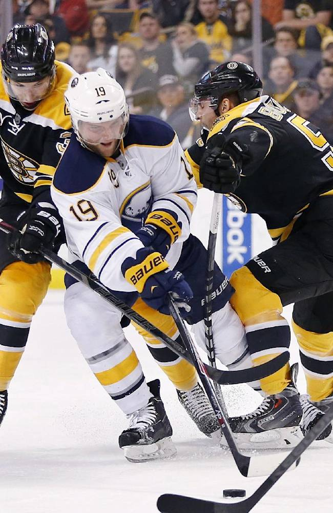 Buffalo Sabres' Cody Hodgson (19) battles Boston Bruins' Jordan Caron (38) and Johnny Boychuk (55) for the puck during the first period of an NHL hockey game in Boston, Saturday, April 12, 2014