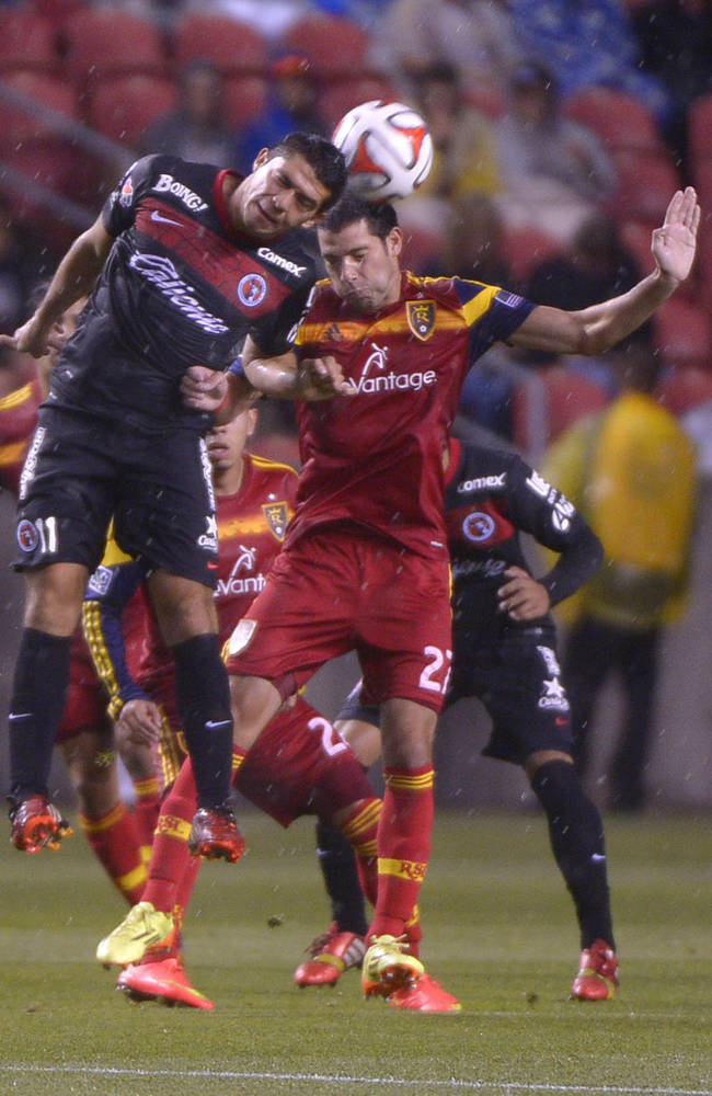 Real Salt Lake midfielder John Stertzer (27) and Club Tijuana's forward Henry Martin. Mexican team Club Tijuana is tied 0-0 with Real Salt Lake after the first half of play, Tuesday, Aug. 12, 2014, at Rio Tinto Stadium in Sandy, Utah