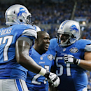Detroit Lions running back Reggie Bush (21) is congratulated by teammates tackle Cornelius Lucas (77) and center Dominic Raiola (51) after his 26-yard rushing touchdown during the second half of an NFL football game against the Green Bay Packers in Detroi