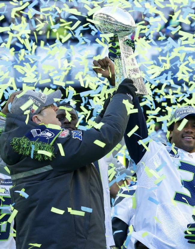 Seattle Seahawks owner Paul Allen, left, lifts the Vince Lombardi Trophy with Seahawks quarterback Russell Wilson (3) during a rally on Wednesday, Feb. 5, 2014, in Seattle. The Seahawks defeated the Denver Broncos on Sunday in NFL football's Super Bowl XLVIII game in East Rutherford, N.J