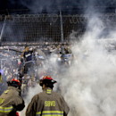 Firemen put off flames after Quilmes's fans lit a fire in the stands during an Argentine league soccer match against River Plate in Buenos Aires, Argentina, Sunday, Dec. 14, 2014 The Associated Press