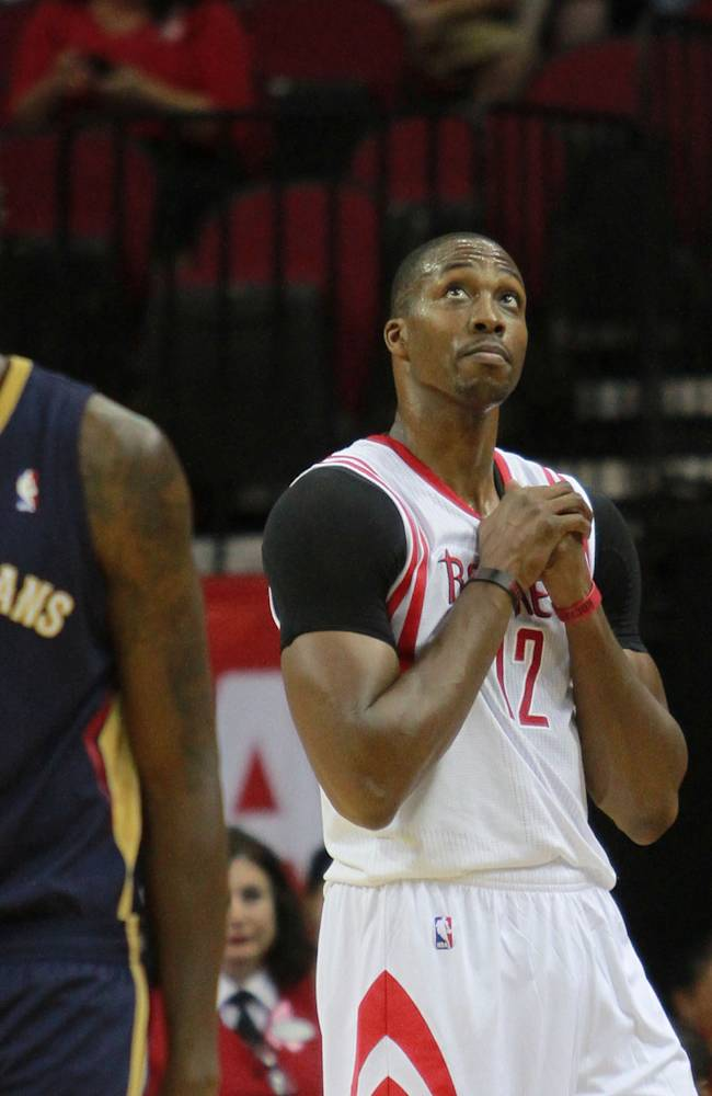 Houston Rockets center Dwight Howard looks to the scoreboard after being called for goaltending against the New Orleans Pelicans during the first half of  a preseason NBA basketball game in Houston, Saturday, Oct. 5, 2013