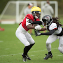 Atlanta Falcons safety Dezmen Southward, right, hands off wide receiver Freddie Martino, during a training session at the Arsenal FC training ground in London Colney, England, Wednesday Oct. 22, 2014. The Falcons will play the Detroit Lions in an NFL foot