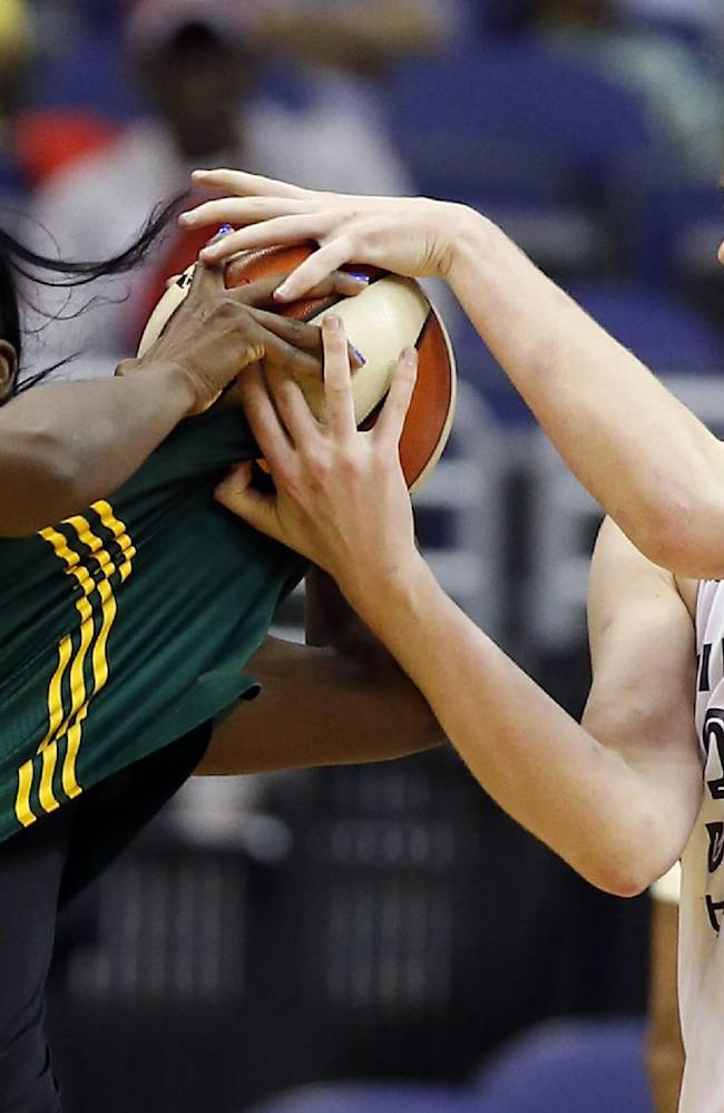Seattle Storm's Crystal Langhorne (1) tries to hang on to the ball as Washington Mystics center Emma Meesseman, from Belgium, grabs the ball and part of her jersey, during the first half of a WNBA basketball game Saturday, May 24, 2014, in Washington. The Storm won 73-65