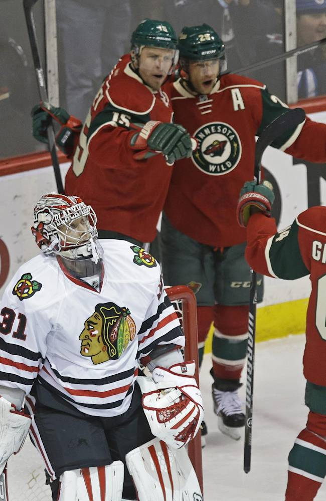Chicago Blackhawks goalie Antii Raanta, left, of Finland, looks toward the replay as Minnesota Wild's Dany Heatley, top left, and Jason Pominville celebrate Pominville's goal in the first period of an NHL hockey game, Thursday, Jan. 23, 2014, in St. Paul, Minn