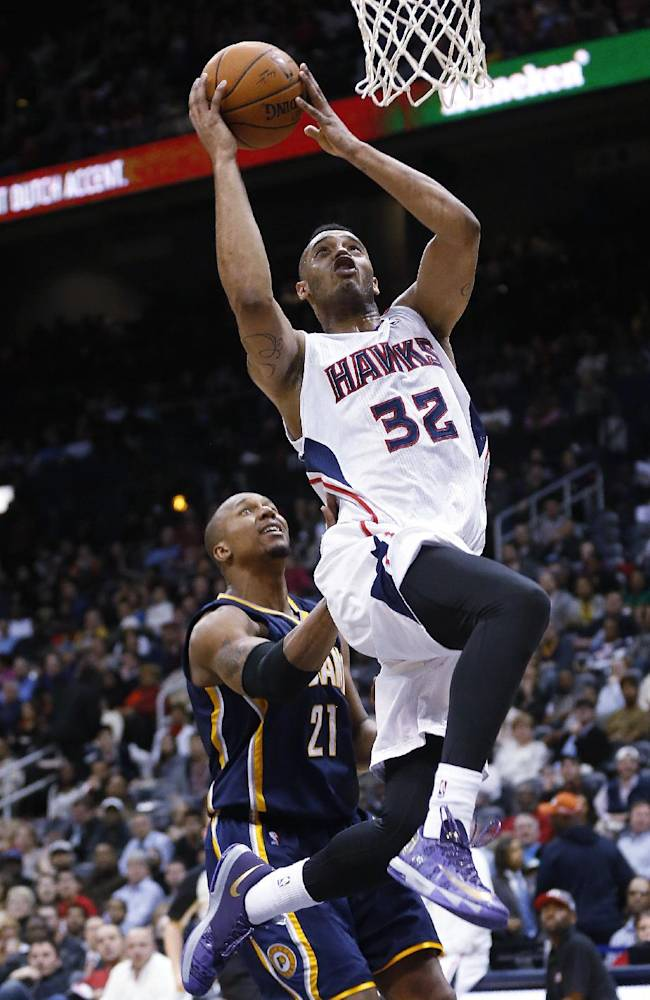 Atlanta Hawks power forward Mike Scott (32) is fouled by Indiana Pacers power forward David West (21) as he scores in the second half of an NBA basketball game, Tuesday, Feb. 4, 2014, in Atlanta. Indiana won 89-85