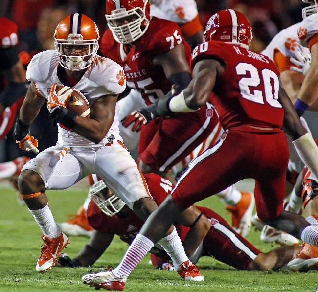 Clemson's Roderick McDowell (25) tries to avoid the tackle of North Carolina State's Hakim Jones (20) during the second half of an NCAA college football game in Raleigh, N.C., Thursday, Sept. 19, 2013. McDowell had 68 yards rushing in Clemson's 26-14 win