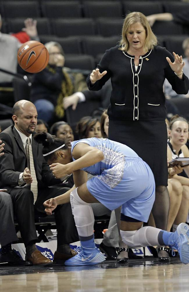 North Carolina's Allisha Gray, left, falls out of bounds as Wake Forest head coach Jen Hoover, top right, watches during the first half of an NCAA college basketball game in Winston-Salem, N.C., Thursday, Jan. 23, 2014