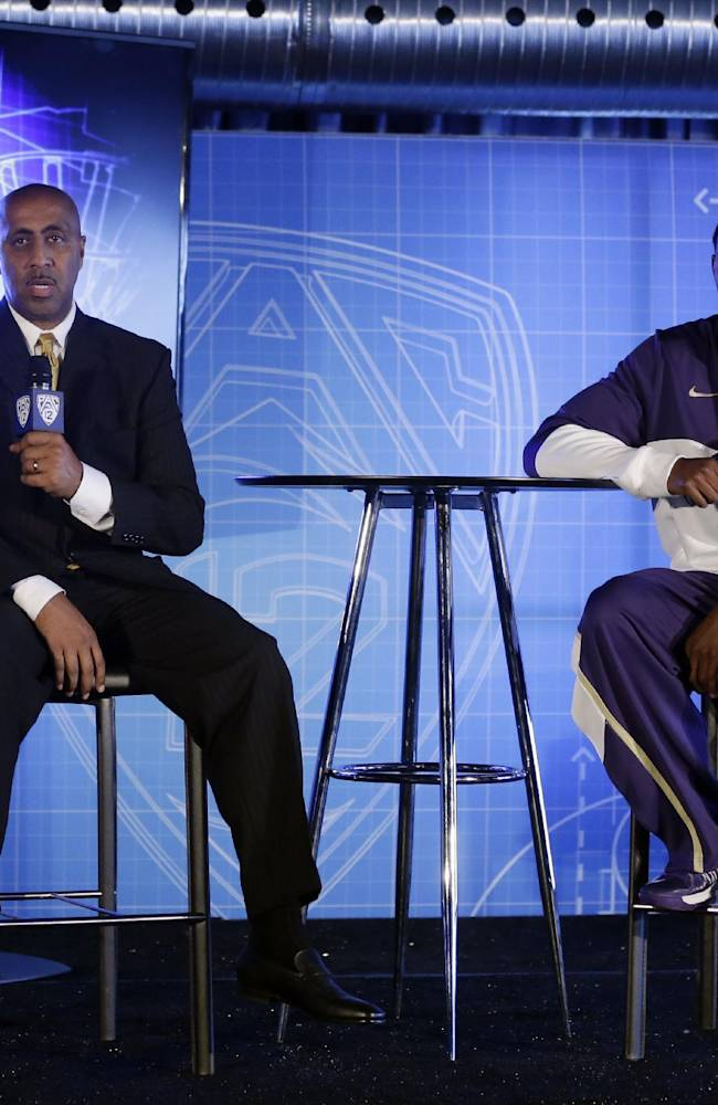 Washington head coach Lorenzo Romar, left, answers questions alongside C.J. Wilcox during the Pac-12 NCAA college basketball media day on Thursday, Oct. 17, 2013, in San Francisco