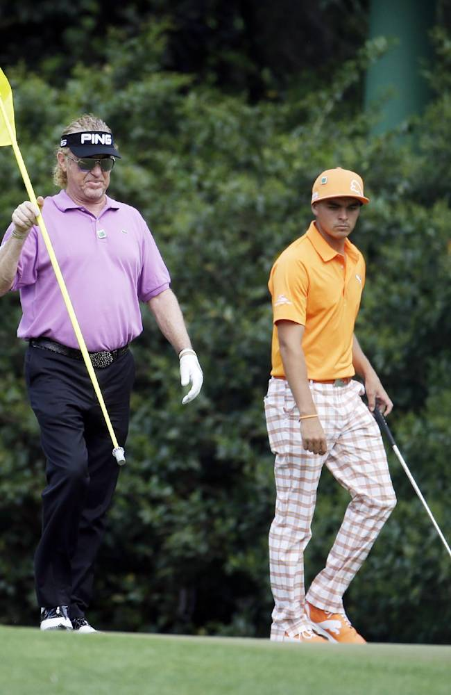 Rickie Fowler, right, watches as Miguel Angel Jimenez, of Spain, puts a flag back in the cup on the 11th green during the fourth round of the Masters golf tournament Sunday, April 13, 2014, in Augusta, Ga