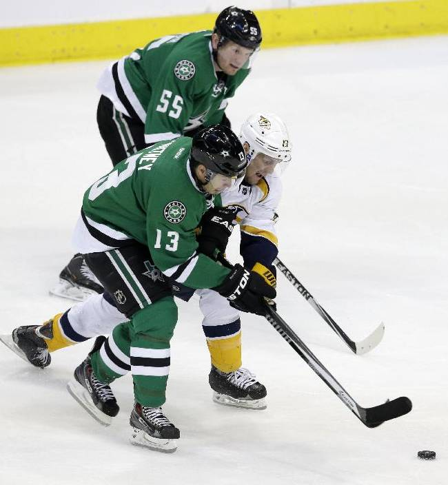 Dallas Stars' Ray Whitney (13) and Sergei Gonchar (55) of Russia combine to take control of a puck in front of Nashville Predators' Nick Spaling (13) in the third period of an NHL hockey game, Friday, March 28, 2014, in Dallas. The Stars won 7-3
