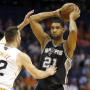 San Antonio Spurs' Tim Duncan (21) looks to pass over Phoenix Suns' Miles Plumlee during the first half of an NBA basketball game, Wednesday, Dec. 18, 2013, in Phoenix. (AP Photo/Matt York)