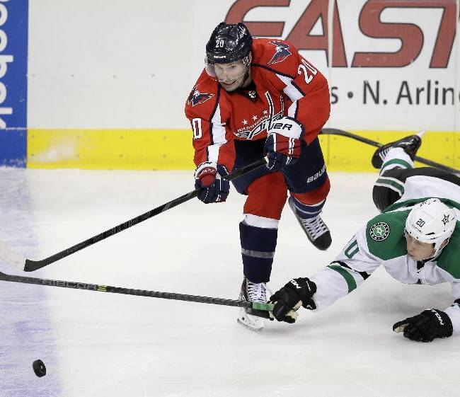 Washington Capitals' Troy Brouwer (20) passes as Dallas Stars' Cody Eakin (20) dives forward while attempting to intercept in the third period of an NHL hockey game on Saturday, Oct. 5, 2013, in Dallas. The Stars won 2-1