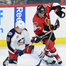 Ottawa Senators' Chris Neil, right, fights for the puck against Columbus Blue Jackets' Matt Calvert during third period NHL hockey action in Ottawa, Ontario, on Saturday, Oct. 18, 2014 The Associated Press